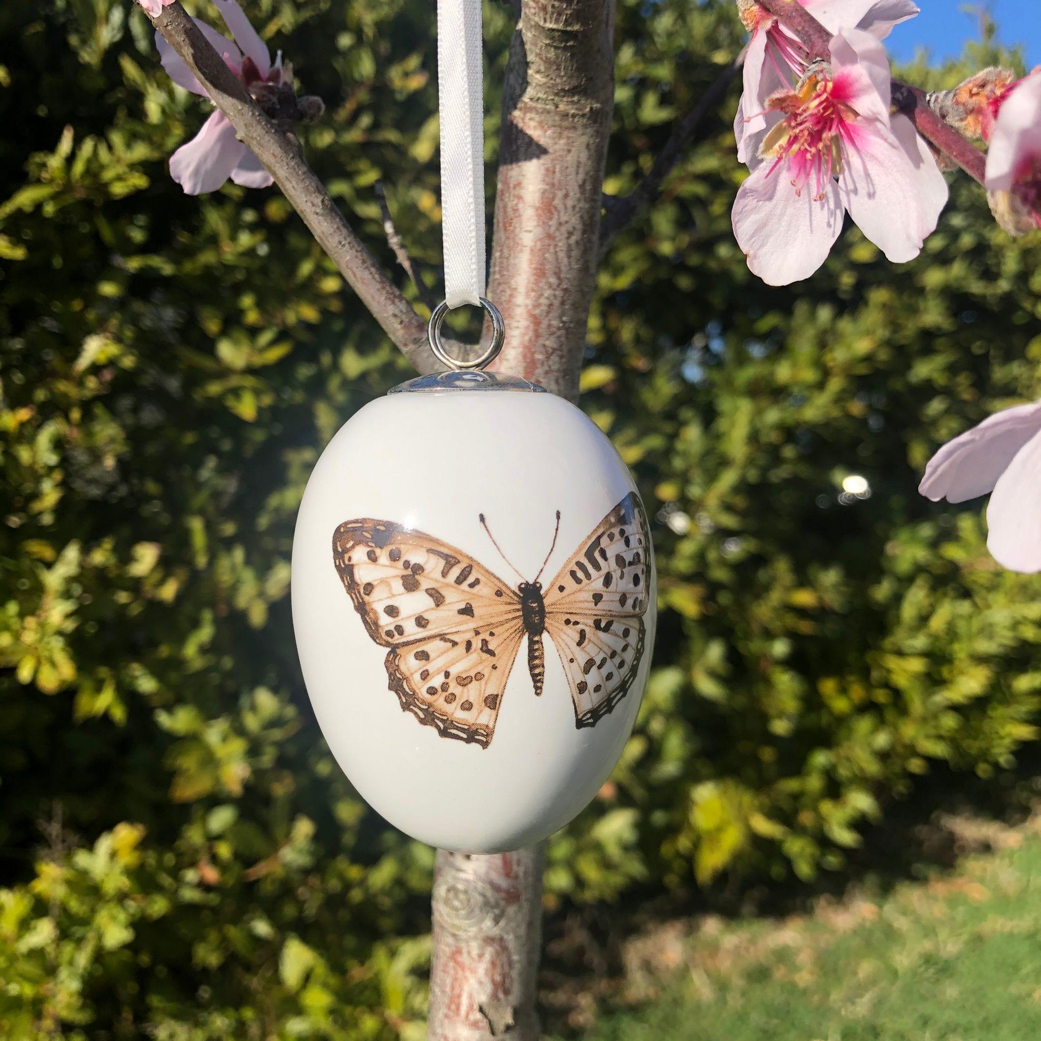 Uovo di porcellana con farfalla marrone